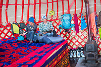 Two people inside a yurt, reading and relaxing, while on a ski touring trip in Kyrgyzstan
