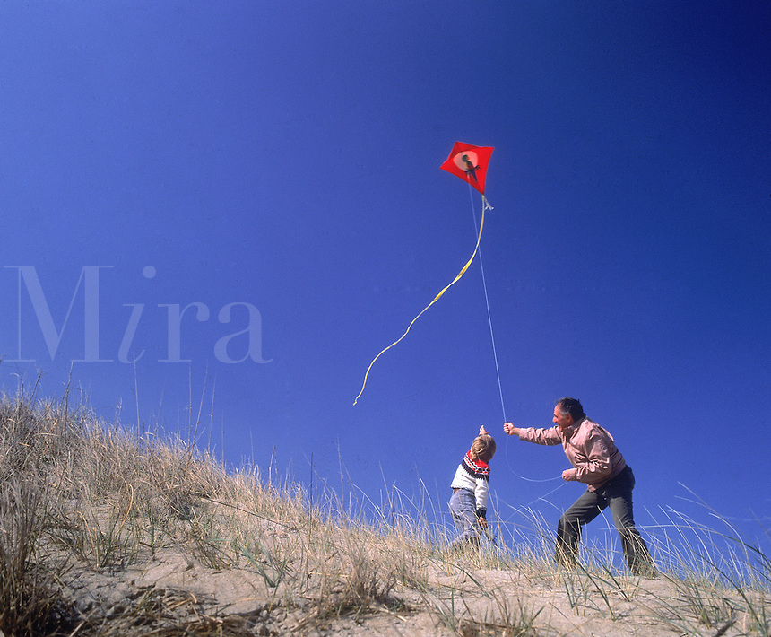 Father and child flying kite.
