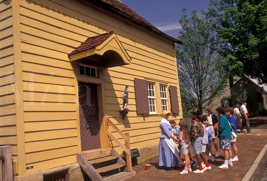 AJ3395, Old Salem, Moravian, Winston-Salem, North Carolina, A group of people listening to an interpreter outside the Miksch House in Old Salem, a living history restoration of the Moravian church town of Salem founded in 1766, in Winston-Salem in the state of North Carolina.