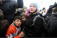 Pictured: A mother and her two children visibly upset Monday 29 February 2016<br /> Re: A crowd of migrants has burst through a barbed-wire fence on the FYRO Macedonia-Greece border using a steel pole as a battering ram.<br /> TV footage showed migrants pushing against the fence at Idomeni, ripping away barbed wire, as FYRO Macedonian police let off tear gas to force them away.<br /> A section of fence was smashed open with the battering ram. It is not clear how many migrants got through.<br /> Many of those trying to reach northern Europe are Syrian and Iraqi refugees.<br /> About 6,500 people are stuck on the Greek side of the border, as FYRO Macedonia is letting very few in. Many have been camping in squalid conditions for a week or more, with little food or medical help.