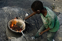 A Haitian man works with melted aluminium to make a kitchen pot in the aluminium recycling shop on the street of Port-au-Prince, Haiti, 11 July 2008.