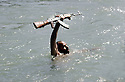 Iraq 1985 Kurdistan,during the armed struggle in Lolan,a peshmerga swimming in a river, holding up his  kalachnikov   Irak 1985 Au Kurdistan, pendant la lutte armée dans le Lolan, peshmerga nageant dans une riviere avec son bras tenant hors de l'eau son arme