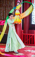 Yangzhou, Jiangsu, China.  Young Woman Performing Traditional Dance with Doll and Swirling Fabric, Slender West Lake Park.