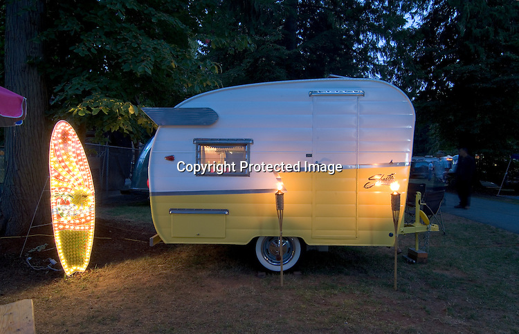 A two-toned white and yellow 1963 Shasta Compact canned ham vintage travel trailer.