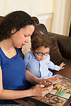 3 year old boy at home with mother, looking at photos on her cell telephone
