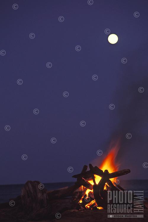 Bonfire at night with moonrise, Kealia Beach, east Kauai.