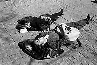 France. Ile-de-france Department. Paris. A loving couple is lying on the ground near the entrance of the Centre Georges Pompidou. The young man with both eyes closed sings a song and plays the guitar while her girlfriend listens to him. She has stopped reading her book Siddhartha by Hermann Hesse. Centre Georges Pompidou, also known as the Pompidou Centre, is a complex in the Beaubourg area. © 1991 Didier Ruef