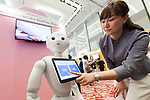 An exhibitor gives a demonstration of robot Pepper's Tax Free Robo program during a media event at Pepper World 2016 exhibition on July 20, 2016, Tokyo, Japan. Kenichi Yoshida, vice president of business development for SoftBank Robotics along with other guests spoke about the new features of Pepper such as Chinese response and speech recognition, and duty free tax refunds and electronic payments services, in response to business needs. Pepper for Biz 2.0 press conference was held a day before the start of Pepper World 2016 exhibition, where developers will introduce applications for SoftBank's robot Pepper. Pepper World will run until July 22. (Photo by Rodrigo Reyes Marin/AFLO)