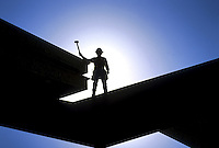 Steel worker on steel beam on new construction at sunrise. California.