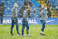 Kal Naismnith (24) of Luton Town (left) surveys the pitch with Luton Town players as snow falls ahead of  the FA Cup 4th round behind closed doors match between Chelsea and Luton Town at Stamford Bridge, London, England on 24 January 2021. Photo by David Horn.