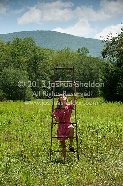 Woman climbing wooden ladder in field