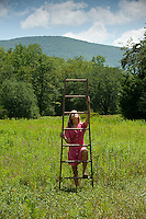 Woman climbing wooden ladder in field