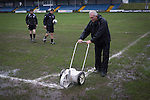 Port Talbot Town 3 Caerau Ely 0, 06/02/2016. Genquip Stadium, Welsh Cup fourth round. A groundsman painting the lines under the supervision of match officials before Port Talbot Town played host to Caerau Ely in a Welsh Cup fourth round tie at the Genquip Stadium, formerly known as Victoria Road. Formed by exiled Scots in 1901 as Port Talbot Athletic, they competed in local and regional football before being promoted to the League of Wales  in 2000 and changing their name to the current version a year later. Town won this tie 3-0 against their opponents from the Welsh League, one level below the welsh Premier League where Port Talbot competed, watched by a crowd of 113. Photo by Colin McPherson.