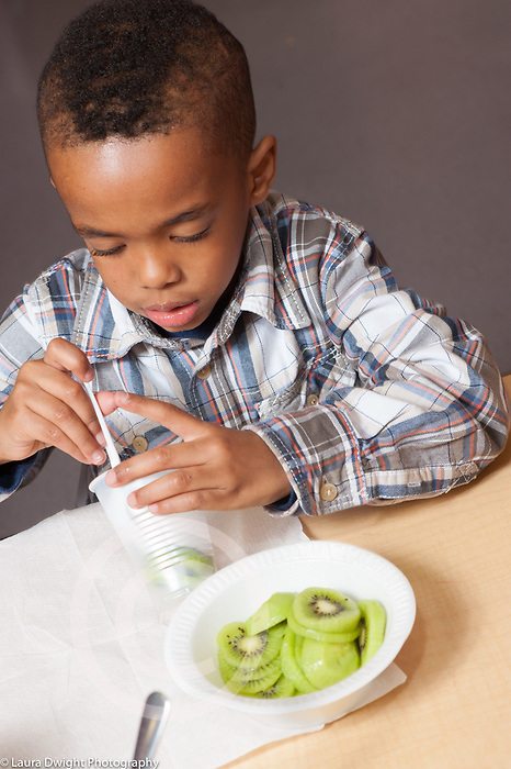 Education preschool 3-4 year olds meals breakfast boy eating fruit kiwi fruit