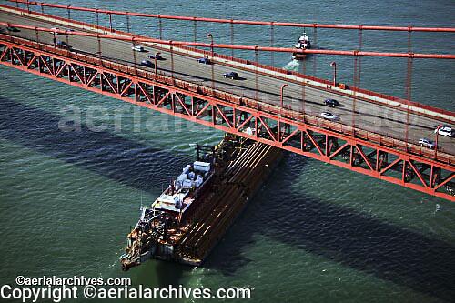 aerial photograph tug and barge passing under Golden Gate bridge, San Francisco, California