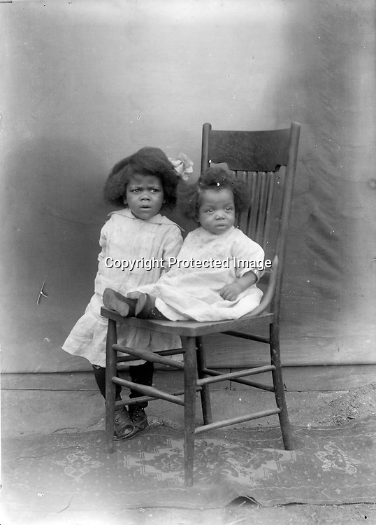 """PAIRS OF SIBLINGS. It appears that John Johnson sometimes set up his open-air """"studio"""" and families brought their children to him. It is difficult to be certain whether this image and image LB055 were taken the same day, but they were taken on the same rug and perhaps used the same chair. Baby boys and girls were often dressed similarly, but hair ribbons were huge and hugely popular for girls only.<br /> <br /> Photographs taken on black and white glass negatives by African American photographer(s) John Johnson and Earl McWilliams from 1910 to 1925 in Lincoln, Nebraska. Douglas Keister has 280 5x7 glass negatives taken by these photographers. Larger scans available on request."""