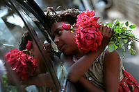A young flower seller on the side of the road attempts to sell roses to passing commuters in cars and buses.