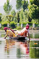 Kashmiri women in headscarves washing laundry from their traditional shikara, Dal Lake, Srinagar, Kashmir, India.