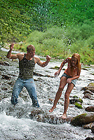 Young couple splashing each other in a stream