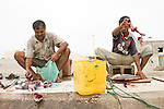 Two fisherman clean their catch of the day in Mirbat - Oman - National Geographic Traveler