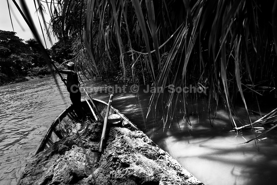 A Colombian sand miner, using a barge pole, navigates his boat loaded with extracted sand in the river La Vieja in Cartago, Colombia, 13 April 2013. Artisanal (unmechanised) sand mining is an ancient mining technique used to obtain sand for construction purposes. Depending on the natural conditions (strength of the stream, depth of the river etc.), together with the sand miners' physical condition, the material is extracted in metal buckets, either by standing on the river bottom and searching for sand by feet, or, diving up to 3-5 meters deep using a wooden plank with steps. In spite of the physically demanding work, a sand miner's daily salary does not exceed 15-20 US dollars. However, the sand miners are very proud of their profession, valuing their work freedom above all, and usually, as long as their health and strength permit, they keep facing the river stream.