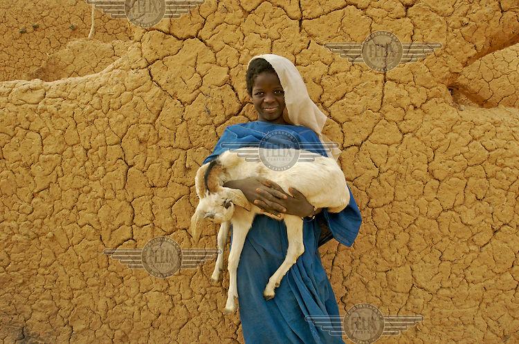 A girl stands holding a goat in the village of Intedeyne.