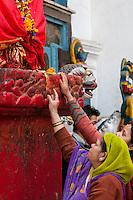 Nepal, Kathmandu.  Hindu Women Placing Flower Offerings at Foot of Hanuman Statue, Durbar Square.