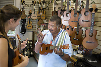 Woman playing an ukulele at Mele Ukulele store in Wailuku, Maui