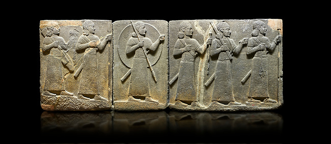 Hittite relief sculpted orthostat stone panel of Royal Buttress Basalt, Karkamıs, (Kargamıs), Carchemish (Karkemish), 900-700 B.C. Warriors. Anatolian Civilisations Museum, Ankara, Turkey.<br /> <br /> Right panel - Three figures each with a long dress, a thick belt and curly hair. The figure in front holds a spear with a broken tip in his left hand and a leafy branch in his right hand. The figure in the middle made his left hand a fist, and he carries a tool with his right hand at the level of his head. They are followed with a figure holding a sceptre in his left hand. All three have each a long sword at their waist. <br /> <br /> Against a black background.