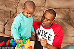Two year old toddler boy at home with father encourage to play with colorful wooden shape sorting peg toy