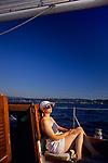 Woman enjoying sailing on a sunny blue sky day on Lake Washington Seattle Washington State