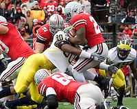 "November 22, 2008. Michigan defensive end Tim Jamison (90) puts a hit on Ohio State running back Chris ""Beanie"" Wells. The Ohio State Buckeyes defeated the Michigan Wolverines 42-7 on November 22, 2008 at Ohio Stadium, Columbus, Ohio."