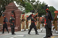 At dusk the Indian and Pakistani flags are lowered at the Wagah (Pakistan) to Attari (India) border crossing on the Grand Trunk Road, accompanied by a display of military drilling by Pakistani (foreground) and Indian (background) soldiers. Thousands of spectators gather every day to cheer each side.