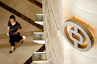 A woman walks under a Bank of China logo at the bank's regional headquarter in Shanghai, China..