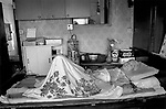 """China, Shanghai. 89 year old  Mr Xu Hou Shen who worked in Hamilton House since the age of seventeen lies on his death bed in his two room apartment at the top of the building. He remembers Hamilton House """"in the good old days"""" when only rich Chinese and foreigners could live there."""