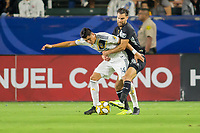 CARSON, CA - SEPTEMBER 15: Joe Corona #14 of the Los Angeles Galaxy and Graham Zusi #8 of Sporting Kansas City battle for a loose ball during a game between Sporting Kansas City and Los Angeles Galaxy at Dignity Health Sports Park on September 15, 2019 in Carson, California.