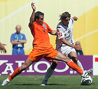 Netherland's Joris Mathijsen (4) and Serbia & Montenegro's Savo Milosevic (9) battle for the ball during a World Cup Group B game at Zentralstadion, Leipzig, Germany, Sunday, June 11, 2006. The Netherlands defeated Serbia and Montenegro 1-0.