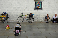 Steet scene near Barkhor street, Lhasa, women praying near the Jokhang Temple, Lhasa, Tibet,.The Jokhang Temple is one of Tibet's holiest shrines, originally built in 647 A.D. in celebration of the marriage of the Tang Princess Wencheng and the Tubo King Songtsen Gampo. In front of the gate is a stone Tablet of Unity from the Tang Dynasty; inscribed are both Chinese characters and Tibetan script. Nearby is the stump of the willow tree said to have been planted by Princess Wencheng herself; two younger willow trees now flank the stump of the first tree...Located in the center of old Lhasa, the temple was built by craftsmen from Tibet, China, and Nepal and thus features different architectural styles. The temple is also the spiritual center of Tibet and the holiest destination for all Tibetan Buddhist pilgrims. In the central hall is the Jokhang's oldest and most precious object--a gold statue of a seated 12-year-old Sakyamuni. This is said to have been transported to Tibet by Princess Wencheng from her home in Changan in 700 A.D. Other precious antiques in the temple include a silk portrait of Buddha from the Tang Dynasty and a pearl gown and gold lamp from the Ming Dynasty. The three-leafed roof of the Jokhang offers splendid views of the bustling Barkhor market and across to the Potala Palace..