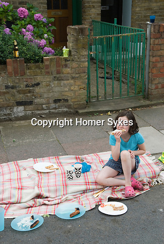 Street Party. The Big Lunch. A young gilr left still eating a sandwich after her friend have left to play.  Brunswick Street Walthamstow Village London E17 England 2009 2000s