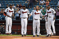 Nashville Sounds Hainley Statia (16), Irving Falu (19), Sean Halton (44) and Hector Gomez (14) wait for catcher Matt Pagnozzi (not pictured) after a walk off home run during the first game of a double header against the Omaha Storm Chasers on May 21, 2014 at Herschel Greer Stadium in Nashville, Tennessee.  Nashville defeated Omaha 5-4.  (Mike Janes/Four Seam Images)