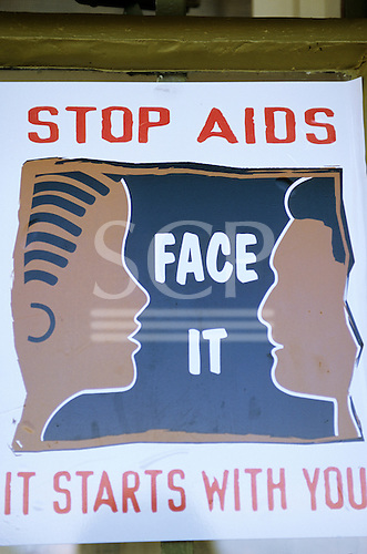 """Lolgorian, Kenya. Public health AIDS poster; """"Stop AIDS Face It It Starts With You""""."""