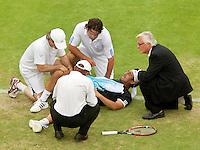 17-6-09, Rosmalen, Tennis, Ordina Open 2009, Raemon Sluiter(M) kijkt bezorgd toe als de fysiotherapeut de verdraaide knie van Baghdatis bekijkt, hij wordt later met de brancard afgevoerd