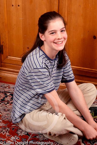 10 year old girl sitting full length portrait smiling vertical Caucasian