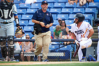 A Binghamton Rumble Ponies trainer comes out to check on left fielder Kevin Kaczmarski (14) during a game against the Hartford Yard Goats on July 9, 2017 at NYSEG Stadium in Binghamton, New York.  Hartford defeated Binghamton 7-3.  (Mike Janes/Four Seam Images)