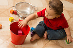 10 month old baby boy sitting on floor throwing block into bucket