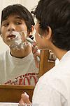 Teenage boy 16 years old shaving himself in bathroom