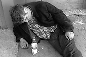 A drunk sleeps on the pavement in North Paddington with an empty bottle of Cinzano