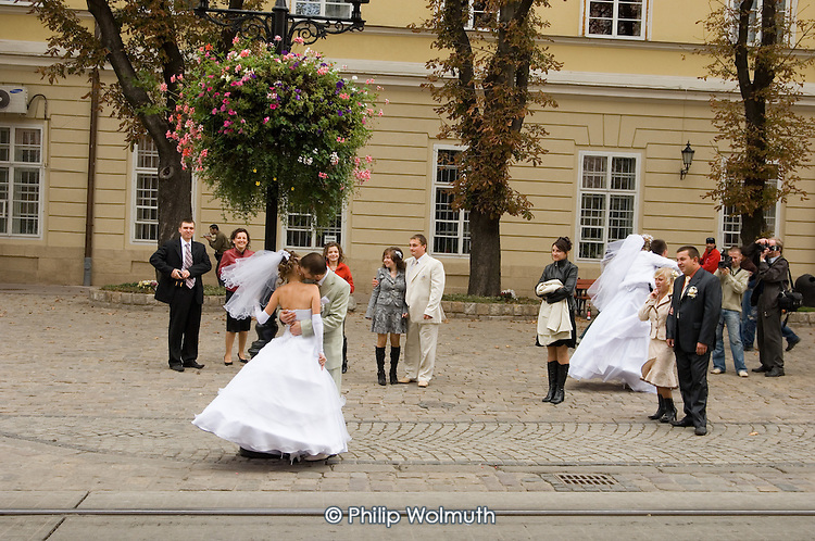 Newly married couples outside the Town Hall in central Lviv.