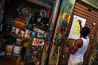 "A Colombian sign painter writes with a brush while working on a music party poster in the sign painting workshop in Cartagena, Colombia, 12 December 2017. Hidden in the dark, narrow alleys of Bazurto market, a group of dozen young men gathered around José Corredor (""Runner""), the master painter, produce every day hundreds of hand-painted posters. Although the vast majority of the production is designed for a cheap visual promotion of popular Champeta music parties, held every weekend around the city, Runner and his apprentices also create other graphic design artworks, based on brush lettering technique. Using simple brushes and bright paints, the artisanal workshop keeps the traditional sign painting art alive."