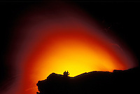 Spectators on cliff watch as Kilauea volcano flows into the Pacific ocean